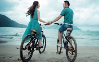 Mini Honeymoon Destinations - Couple On Beach Bikes