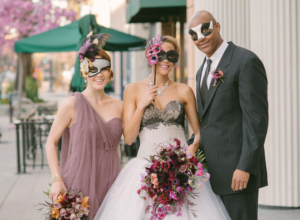 Bride, groom, and maid of honor with Mardi Gras Masks