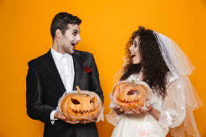 Bride and Groom in Halloween makeup with pumpkins.